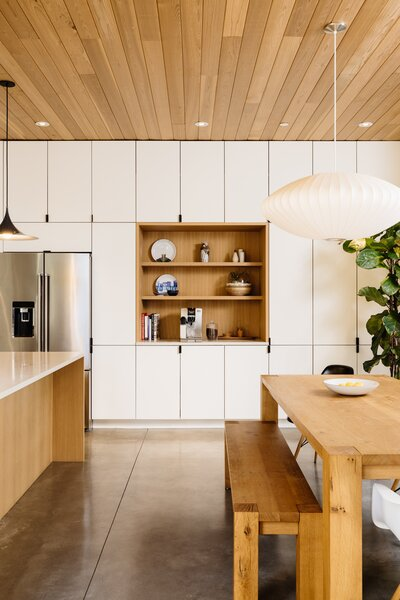 A wall of full-height cabinetry spans one side of the kitchen, complete with inset shelving that provides a dedicated area for the couple's coffee machine and mugs. The space also features a large central island and dining table overlooking the backyard pool.