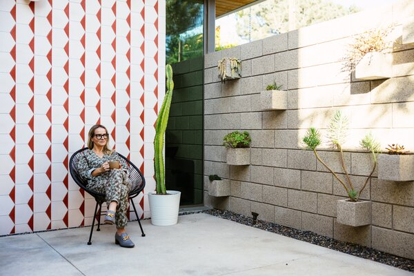 Fittingly named the Courtyard House, the residence features a large outdoor space tucked underneath the cantilevered upper level, providing a quiet and shaded area for Lalita to enjoy her coffee breaks. Rotated masonry blocks extend from the courtyard wall to create succulent planters.