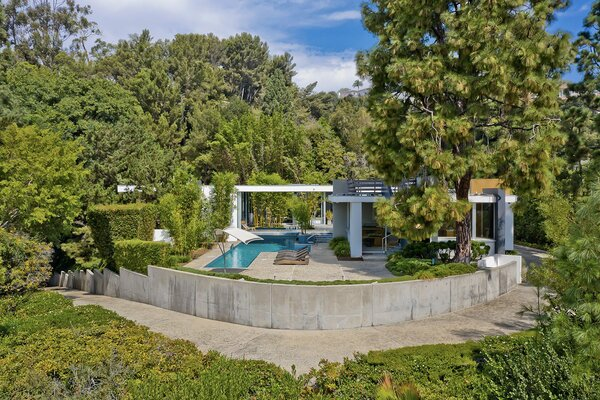 Originally completed by architect Hal Levitt in 1962, the Holt House is sited on a lush lot in Beverly Hills, California. The U-shaped floor plan wraps around a central outdoor area, and the two sides are connected by a bridge-like hallway that spans the pool.