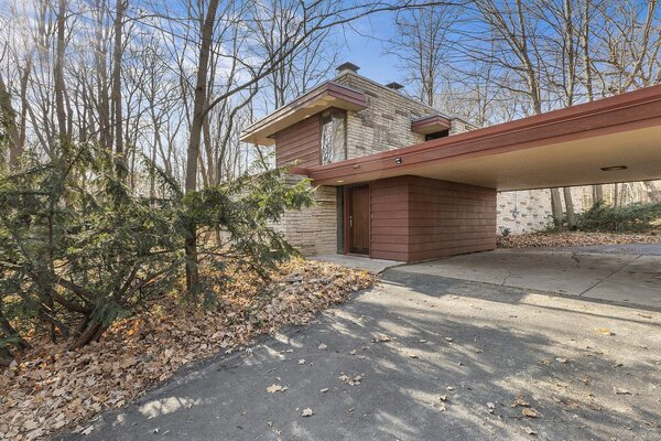 This recently listed home designed by Wisconsin-born architect John Randall McDonald is sited on a 1.20-acre, wooded lot about 15 miles outside of Milwaukee. A single horizontal plane extends from the rectangular structure to form a carport and mark the main entrance.