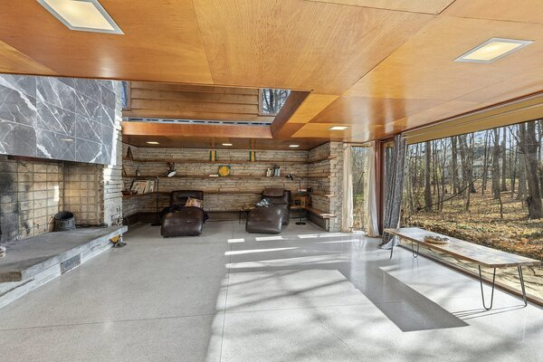 Inside, an inverted floor plan features public areas on the lower level, where floor-to-ceiling windows stretch across the rear facade. In the living room, stacked stone lines an alcove in the corner while the double-height fireplace extends upward into a mezzanine level.