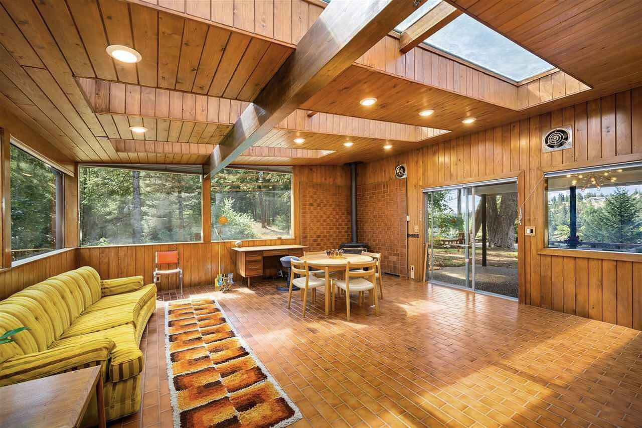 The solarium was added in the 1970s and features several large skylights and wraparound windows. Brown tiles cover the floor and extend up the wall around a corner fireplace.  Photo 7 of 15 in Moritz Kundig's Historic Wallmark House Offers Lakefront Living for $1.1M