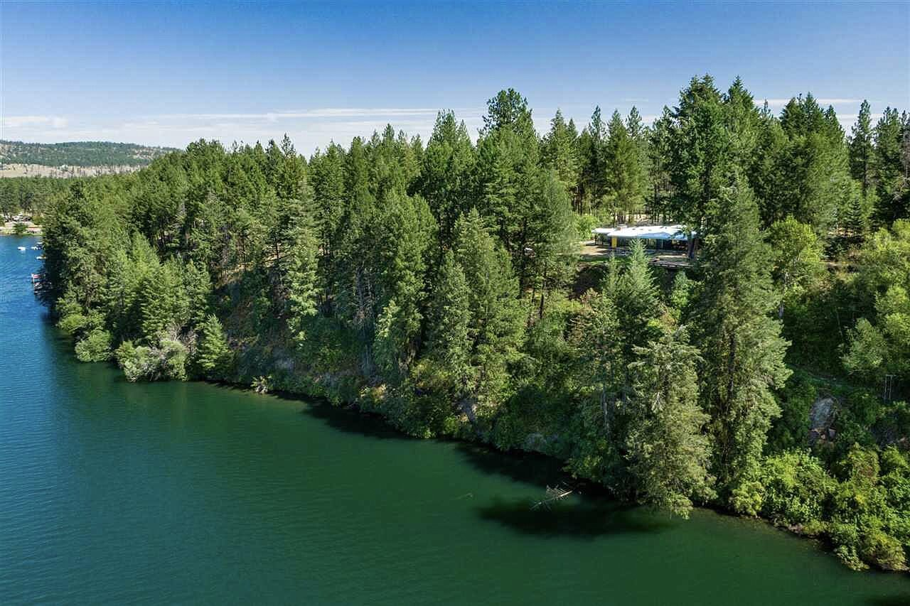 An aerial shot of the property shows the residence's perch on a hilltop above the water.  Photo 15 of 15 in Moritz Kundig's Historic Wallmark House Offers Lakefront Living for $1.1M