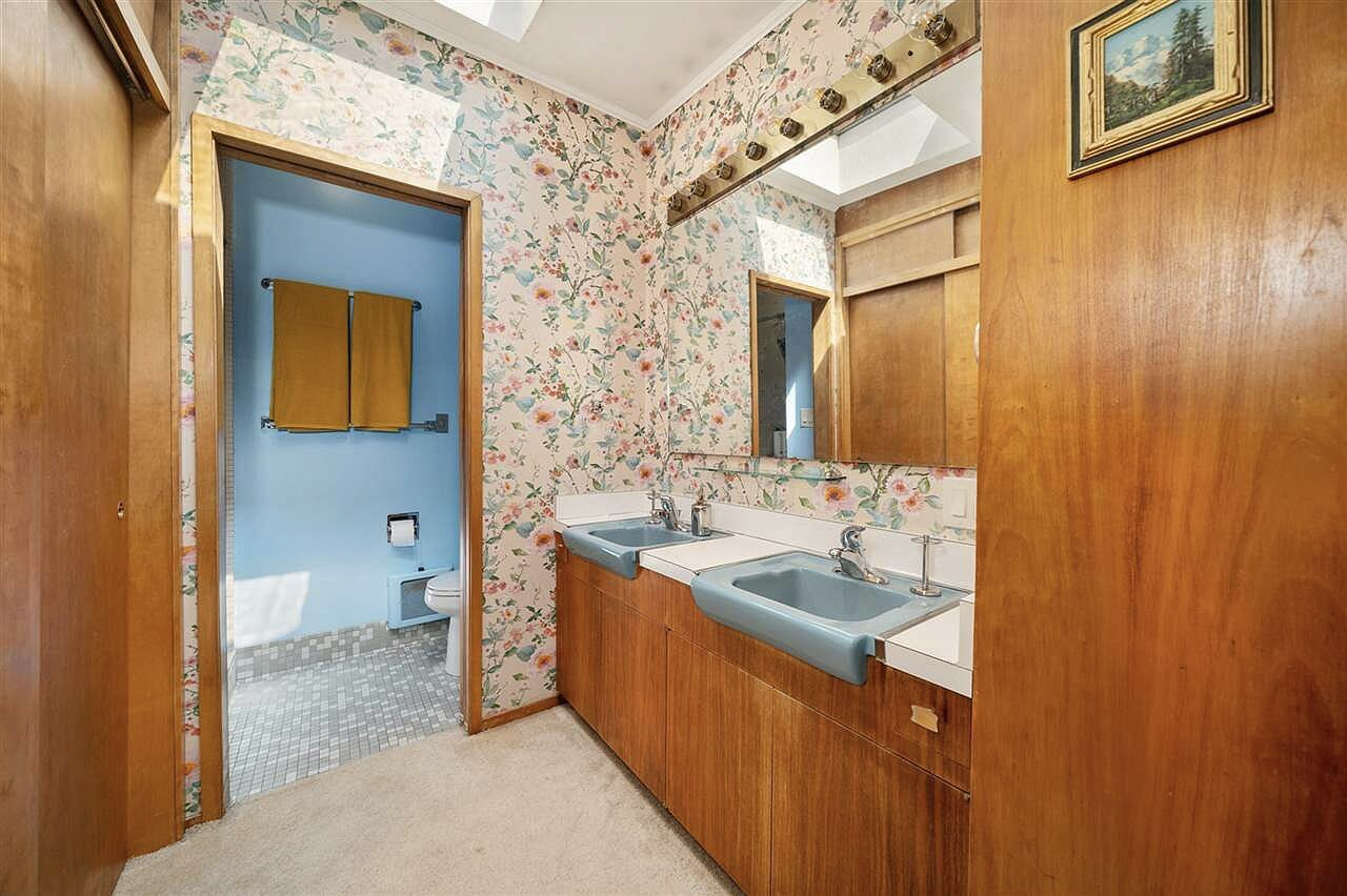 The principal bathroom offers original cabinetry and wood paneling, along with a separate toilet and shower closet.  Photo 11 of 15 in Moritz Kundig's Historic Wallmark House Offers Lakefront Living for $1.1M