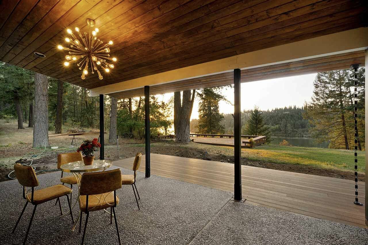 Outside, a covered dining area overlooks the wooded landscape. A deck along the edge of the property provides sweeping views of Long Lake below.  Photo 14 of 15 in Moritz Kundig's Historic Wallmark House Offers Lakefront Living for $1.1M