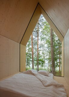 """A closer look at the glazed wall in the sleeping area. """"Kynttilä creates a kind of mental portal to a higher dimension,"""" says the firm. """"The framed nature image turns into an individual abstraction and projection of thoughts."""""""