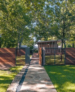 """Rather than expand their midcentury home, Anthony Marks and his partner built a guesthouse on the unused half of their double lot, in Denton, Texas. The gated fence borrows from the material palette used for the dwelling. """"It's like an introduction, or preview, to what lies beyond,"""" says architect Michael Gooden."""