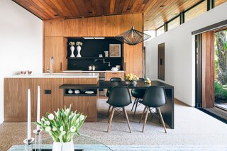 In the kitchen, Eames chairs flank a custom dining table, and the pendant is by Wever & Ducré.