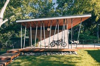 The side patio doubles as a parking spot for a custom-built 1970 Honda CB750.