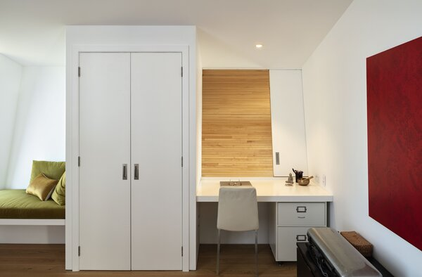 """In her work area, a sliding panel opens to offer Justine a view of the living area below. """"When you're in the house, you're aware of the whole house, which I really like,"""" she says."""