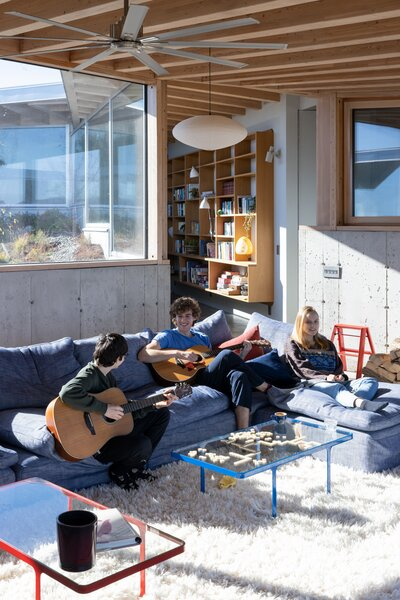 The couple's two sons, Isaac and Charlie, play music with Charlie's girlfriend, Saskia Randle, in the living room, where an Isamu Noguchi Akari lantern hangs above a Cloud sectional from RH Modern.