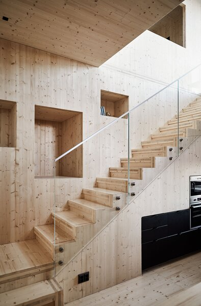 A staircase ascends past inset shelves to the second floor.