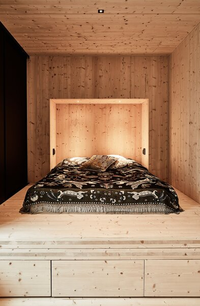The bedroom is lined in spruce and sparsely furnished, save for a built-in bed designed by Ateljé Sotamaa. The coverlet and pillows feature a folkloric pattern by Klaus Haapaniemi & Co.