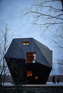 Set in a clearing surrounded by spruce and birch trees in Kontiolahti, Finland, a cabin known as the Meteorite cuts a striking profile. The structure is made entirely of cross-laminated timber (CLT). Air gaps of various sizes behind the facade keep the interior warm without conventional insulation, even during Finland's freezing winters, and give the Meteorite its out-of-this-world shape.