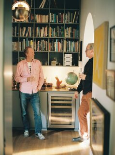 Chris, at left, and Techentin stand in the library, which they outfitted with a solid brass counter. The multi pendant is by Louis Weisdorf and the refrigerator is by U-Line.