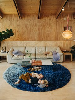 "The couple's baby, Esphyr Rain Superbloom, and Eli lounge next to a MOCA mirrored bench, also by Project Room, and an off-white leather sofa. ""I won't tell you how little we paid for the couch,"" Lizz says of the vintage find. The hand-painted pendant is also by Project Room while the assorted Rowena Sartin pillows are by Iko."