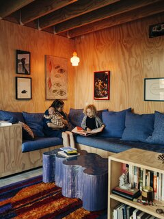In the Dank Lounge, a film screen lowers in front of room-darkening curtains on movie nights. The deep sectional was built by Lizz and Isaac while the Blob coffee table is by Project Room, and the Scandinavian rya rug is vintage. The couple's art collection includes works by many friends and local artists. A print by Alex Smith, along with drawings by Cammie Staros and Karl Haendel, hang in the lounge beside a painting by John Finneran and a photo by Lizz.