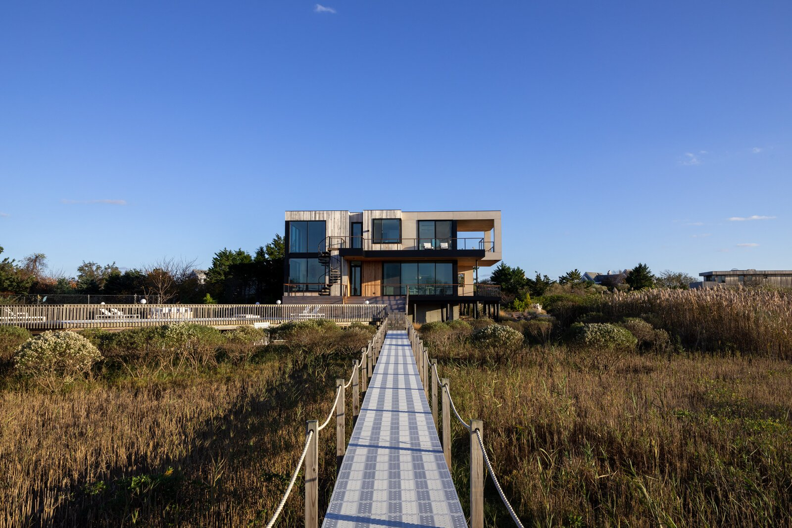 Exterior, Wood Siding Material, Glass Siding Material, Flat RoofLine, and Beach House Building Type Located in Westhampton Beach on New York's Long Island, this recently built home by Josh Manes Architecture is surrounded by preserved wetlands. The house is powered by a solar array on the rooftop while expansive windows, along with cantilevers and recessed sections, address solar heat gains.  Photo 1 of 11 in A New Eco-Friendly Home Emerges From a Tired Structure on Long Island's Wetlands