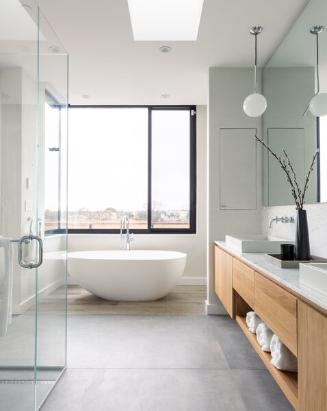 The en suite bathroom features a soaking tub and large windows overlooking the marshy waters.