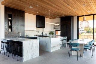 Vermont Danby Marble along the countertops features blue veining that nods to the home's waterfront location. Sliding glass doors open the dining area to the surrounding outdoor space.