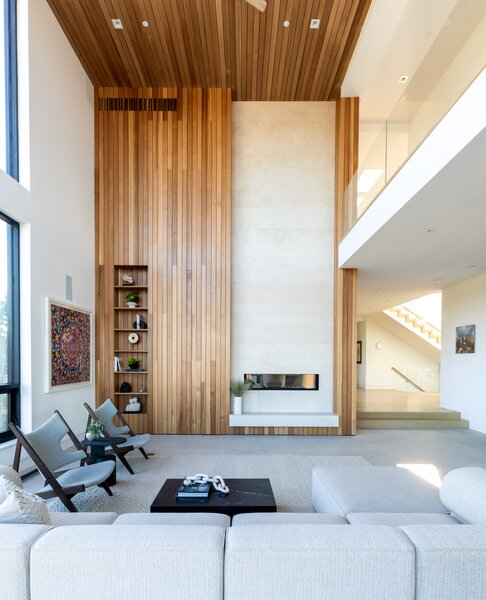 Inside, the voluminous living area features a double-height fireplace clad in cedar and large-format tiles—both of which are echoed along the facade as well. Full-height windows wrap around the opposite corner, providing an abundance of sunlight and helping to naturally heat the space during wintertime.