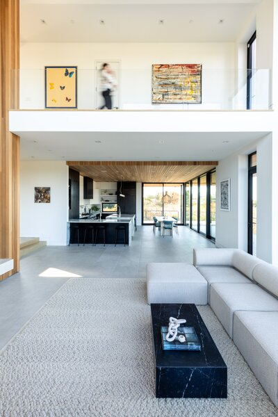 Another perspective of the living area shows the adjacent kitchen and dining room, which feature cedar cladding along the ceiling to visually unite all of the spaces.