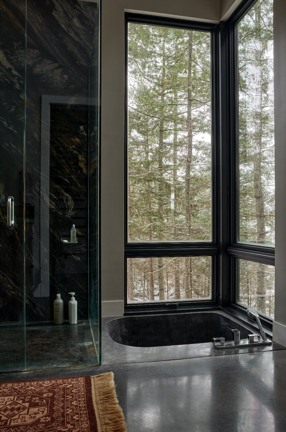 """Bath Room, Marble Wall, Soaking Tub, Marble Counter, and Corner Shower The en suite bathroom is clad in Brazilian marble and features a pair of Ultimate Awning and Picture windows surrounding the sunken tub. """"I see the glass as more than just a transparent barrier to the outside,"""" Peck comments. """"The Marvin windows take a back seat—so much that you don't even notice them.""""  Photo 7 of 12 in A Winding Boardwalk Grounds This Hovering Cabin Along the Edge of a Remote Pond"""