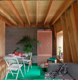 Inside the flat, a bright green resin floor (which is also heated) spans throughout, contrasting against the neutral-toned wood and cement walls. A light pink perforated storage cabinet adds another pop of color to the space.