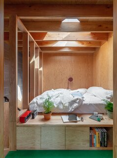 A closer look at the partly enclosed sleeping area, which is illuminated by a small skylight. Custom cabinetry offer deep storage units as a way to help maximize the studio's layout.