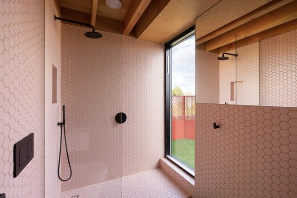 Pink hexagonal tiles line the walls and floor in the bathroom, which has a large glass shower.