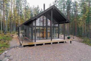 The three-bedroom Iniö model from Pluspuu features floor-to-ceiling windows, a loft-like interior, a wraparound deck, and a gable outline reminiscent of a traditional log cabin.
