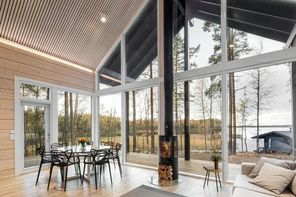 Twenty-foot-tall ceilings and huge windows connect indoors with out. A wood-burning fireplace centers the living-and-dining area.