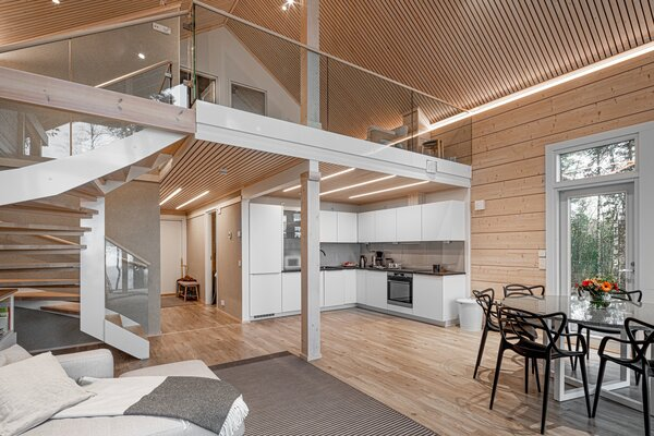 From the living area, a winding staircase leads to the second level with an additional living space and two guest rooms.