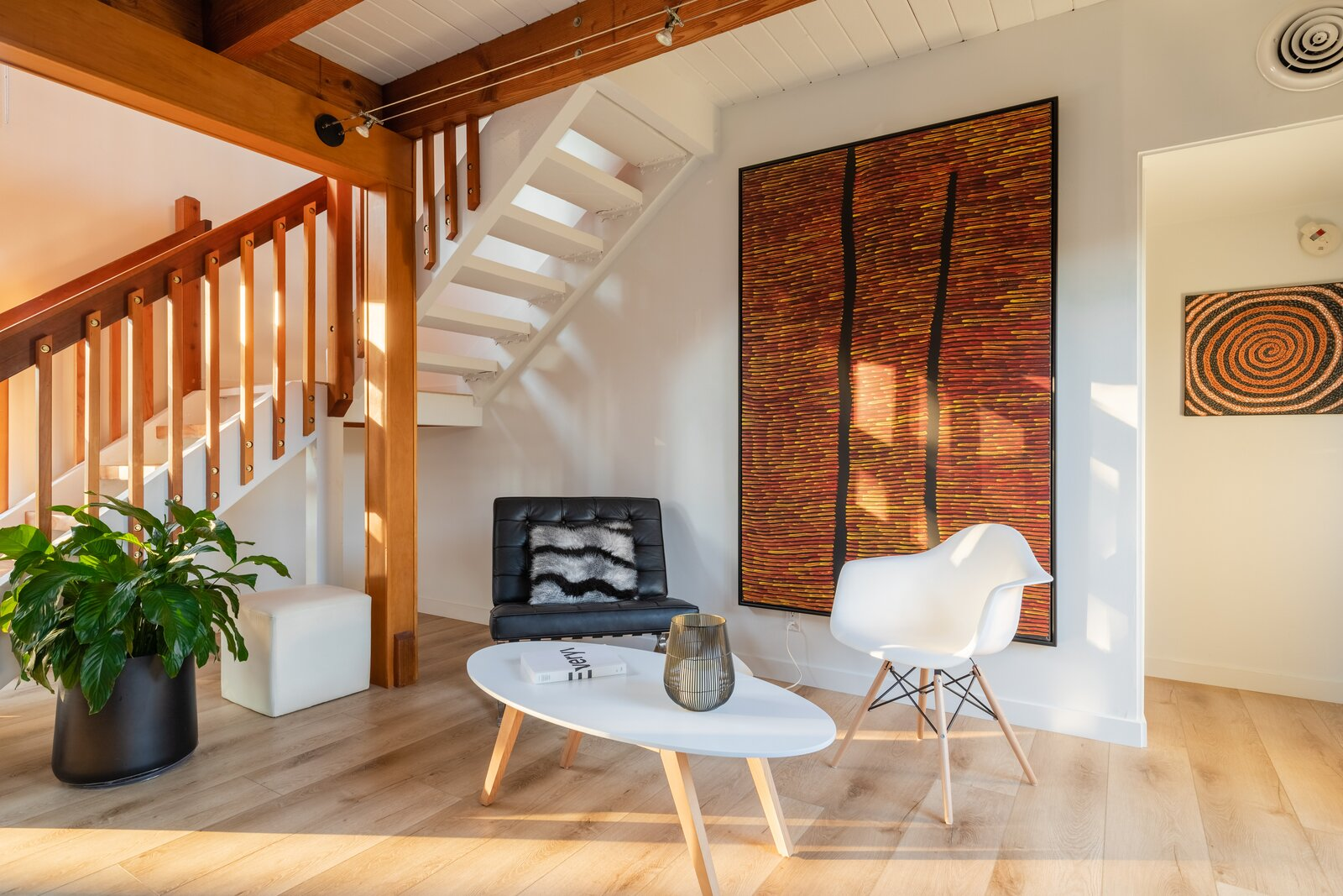 A two-story foyer opens up to one of the home's bright and airy living spaces. Exposed beams pop against the surrounding white walls.  Photo 2 of 12 in A Renovated Cliff May–Designed Home in a Historic SoCal Enclave Asks $1.5M