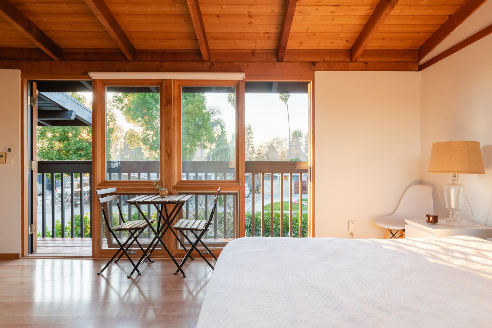 A look at the upper-level bedroom, complete with a private balcony overlooking the front yard.   Photo 11 of 12 in A Renovated Cliff May–Designed Home in a Historic SoCal Enclave Asks $1.5M