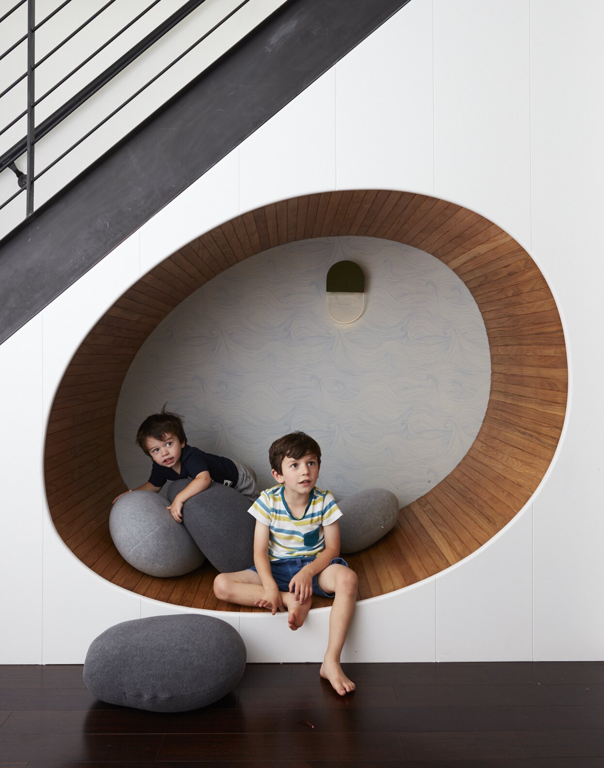 An area underneath a cellar staircase becomes an egg-shaped play area in Tang's hands. The white oak–lined nook features Abigail Edwards wallpaper with a subtle wave pattern.  Photo 5 of 13 in How to Design a Room That Grows Up With Your Kids