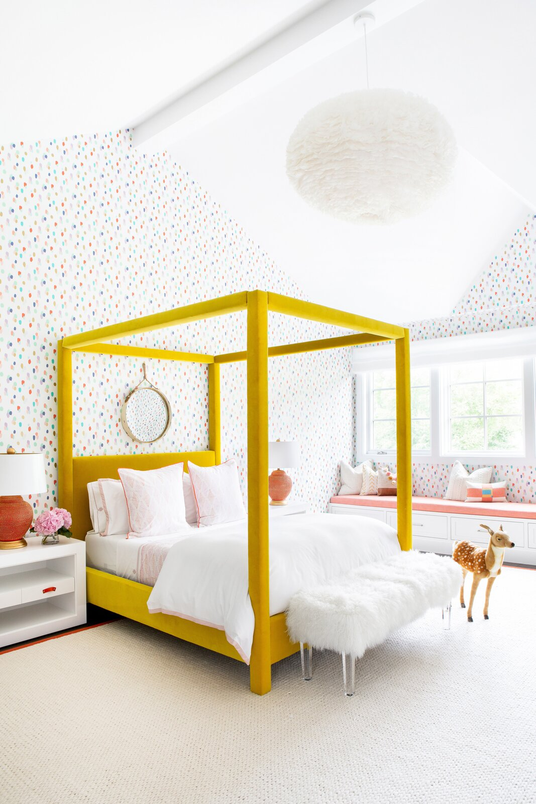 At the Silo Ridge Farmhouse by Chango & Co., a cheery yellow canopy bed by Jayson Home and dotted wallpaper from Brewster Home create a vibrant girl's bedroom.  Photo 11 of 13 in How to Design a Room That Grows Up With Your Kids