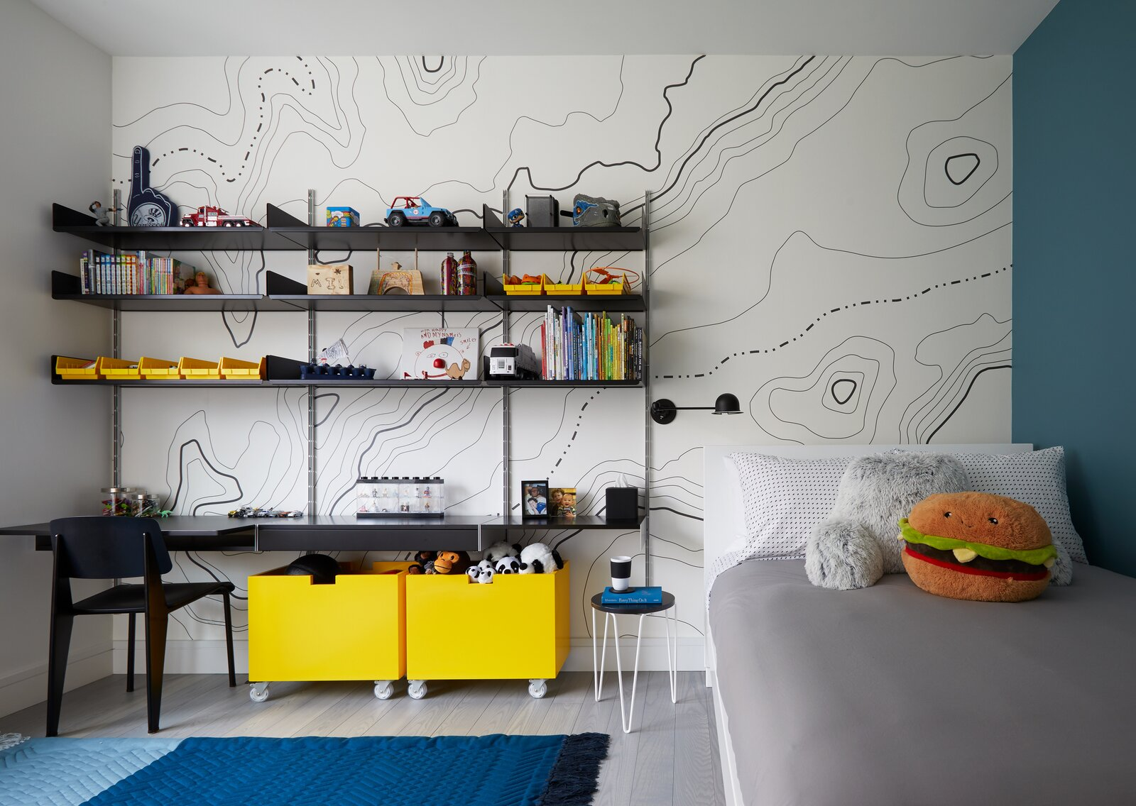 "The parents of a five-year-old boy feared that his room would read ""too young"" when he grew up, so Tang infused the space with elements that would balance fun and flexibility. A graphic topological map from HappyWall and yellow color blocking add youthfulness while Vitsoe modular shelving and custom bins on casters ensure that the room can be adjusted.  Photo 6 of 13 in How to Design a Room That Grows Up With Your Kids"
