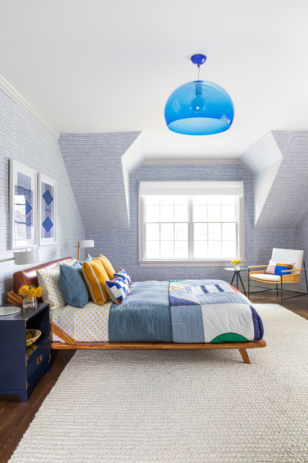 A boy's bedroom by Chango & Co. pairs a queen bed from Crate and Barrel with a bulbous blue light from Hive. The wallpaper is from Holly Hunt.  Photo 12 of 13 in How to Design a Room That Grows Up With Your Kids