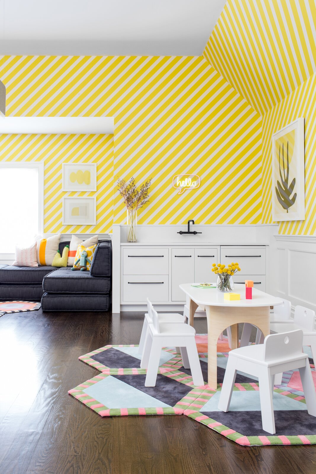 A playroom in Rumson, New Jersey, designed by Chango & Co. features a kitchenette and bold, striped yellow wallpaper. The table and chairs are from Land of Nod, and underfoot is a rug from Kinder MODERN.  Photo 9 of 13 in How to Design a Room That Grows Up With Your Kids