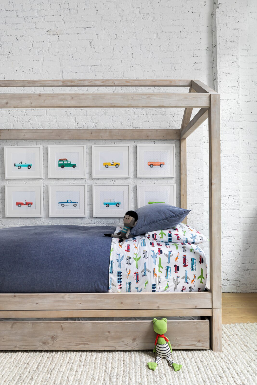 Chango & Co. renovated a young family's loft in Dumbo, Brooklyn, adding a canopy bed from RH Baby & Child and bedding from Pottery Barn Kids in the boy's bedroom. Car artwork from Leslee Mitchell carries out the transportation theme.  Photo 13 of 13 in How to Design a Room That Grows Up With Your Kids