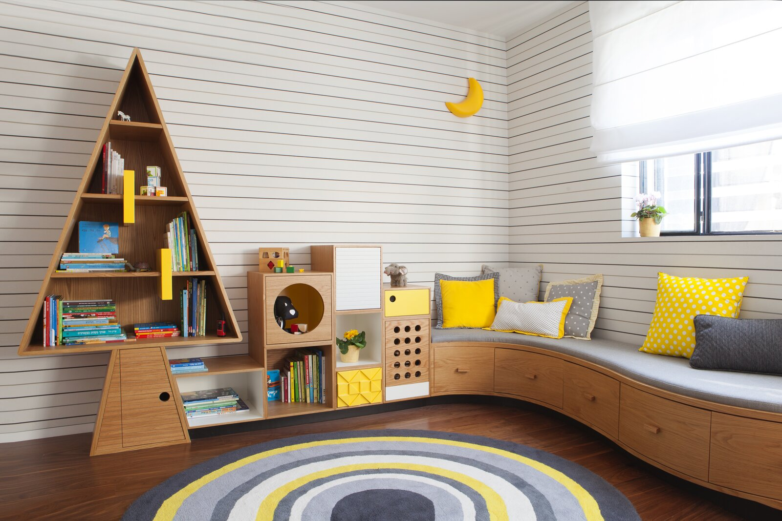 For a family with three kids, Hay fashioned a custom tree-like shelving unit that connects to a curvaceous, built-in sofa—ideal for lounging and reading. Yellow accents brighten up the restrained wooden palette.  Photo 2 of 13 in How to Design a Room That Grows Up With Your Kids