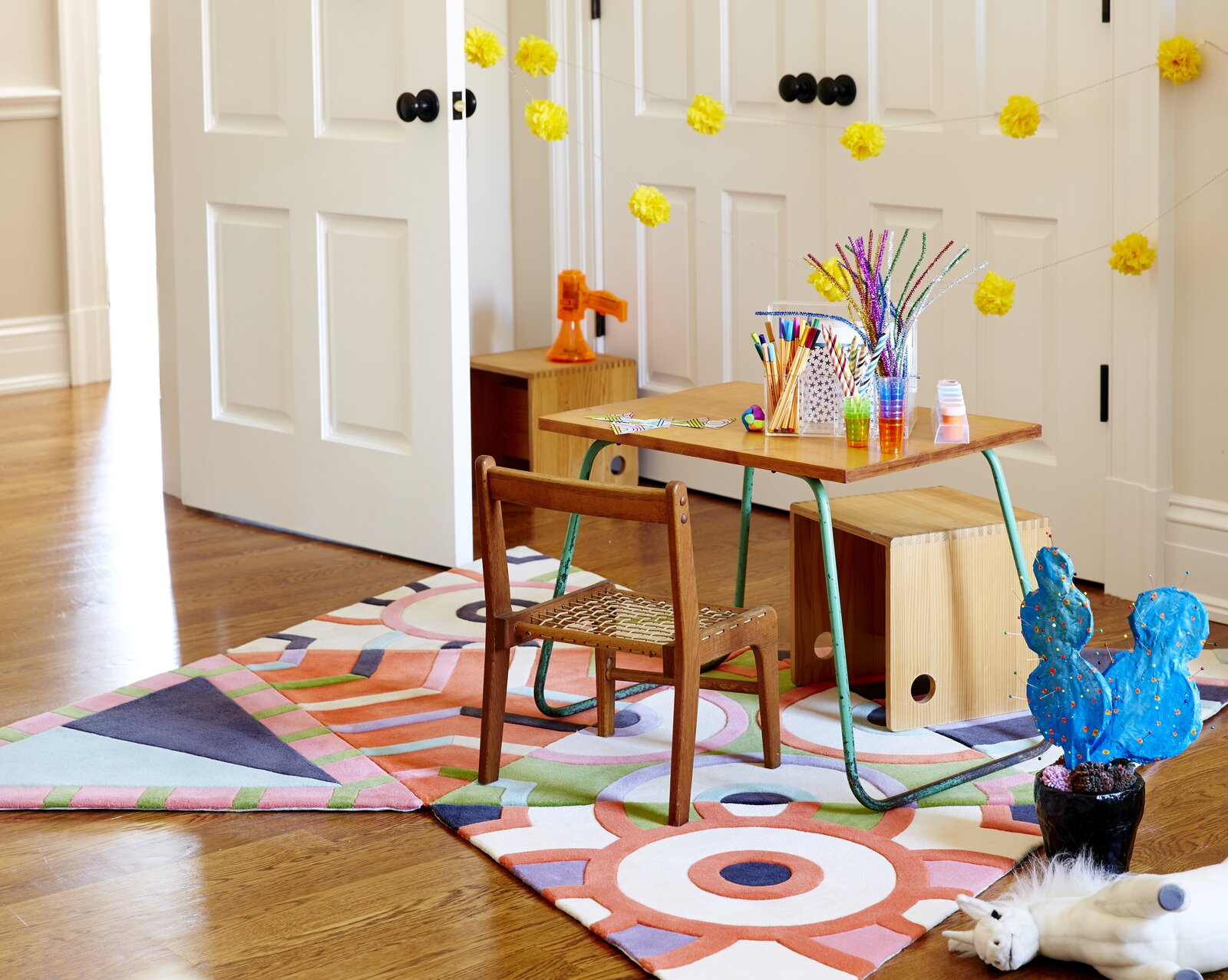 A modular rug by Kinder MODERN adds zest to a petite activity area.  Photo 7 of 13 in How to Design a Room That Grows Up With Your Kids