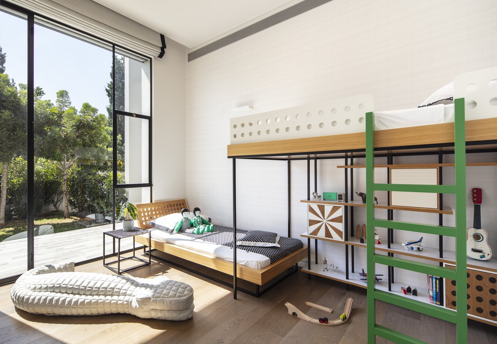 In Herzliya, a suburb of Tel Aviv, designer Sarit Shani Hay created a bedroom for two boys aged three and six. The two beds, arranged at staggered heights, provide the benefits of a bunk bed while allowing storage space.  Photo 1 of 13 in How to Design a Room That Grows Up With Your Kids