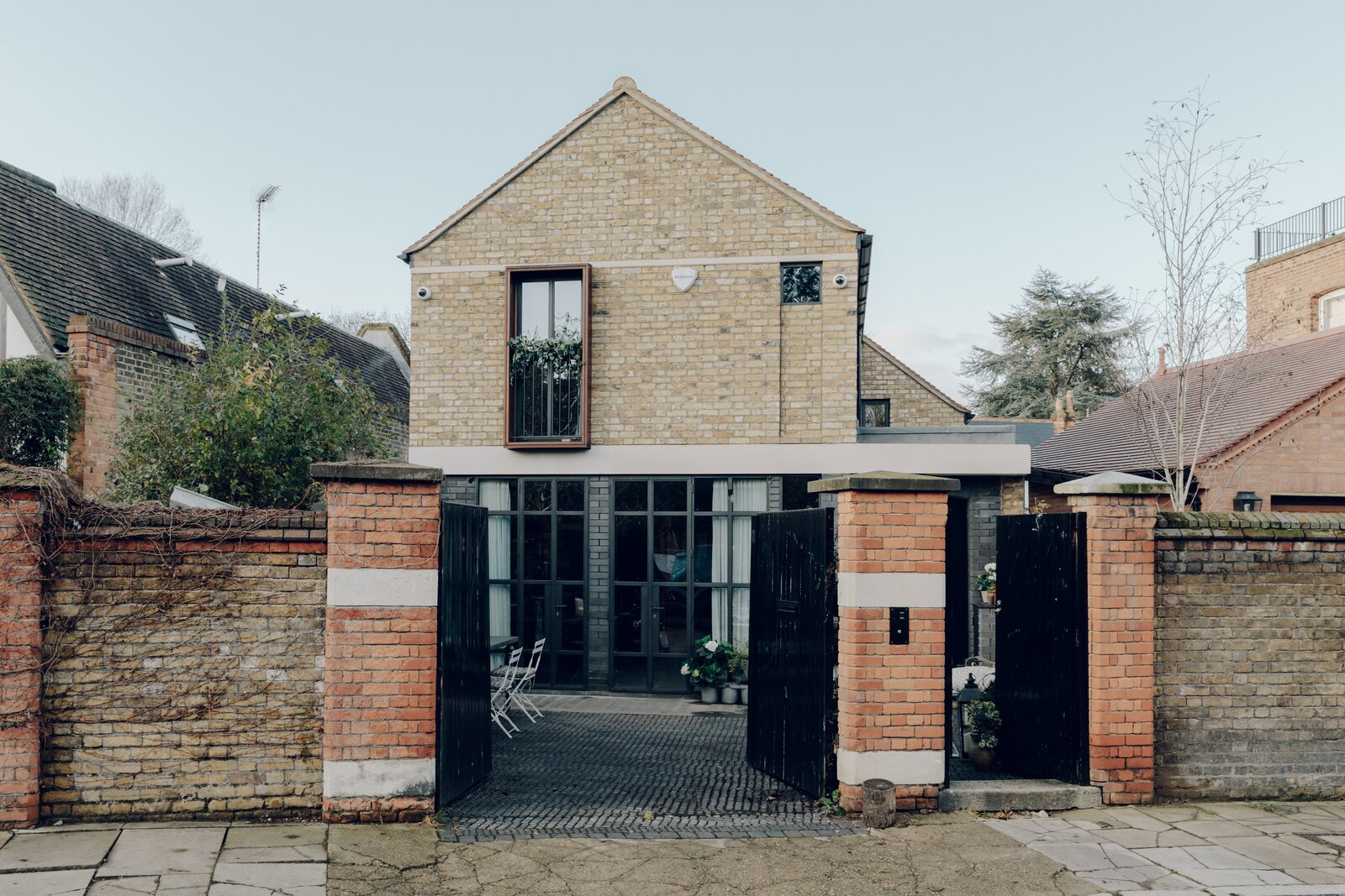 Completed in 2019, this home by London's TDO Architecture picks up on the local vernacular with a stately brick facade set behind a traditional courtyard entrance. Crittall steel-framed glass doors along the lower level set the stage for industrial-style finishes throughout the interior.  Photo 1 of 13 in An Enchanting, Reimagined Coach House in London Asks £2M