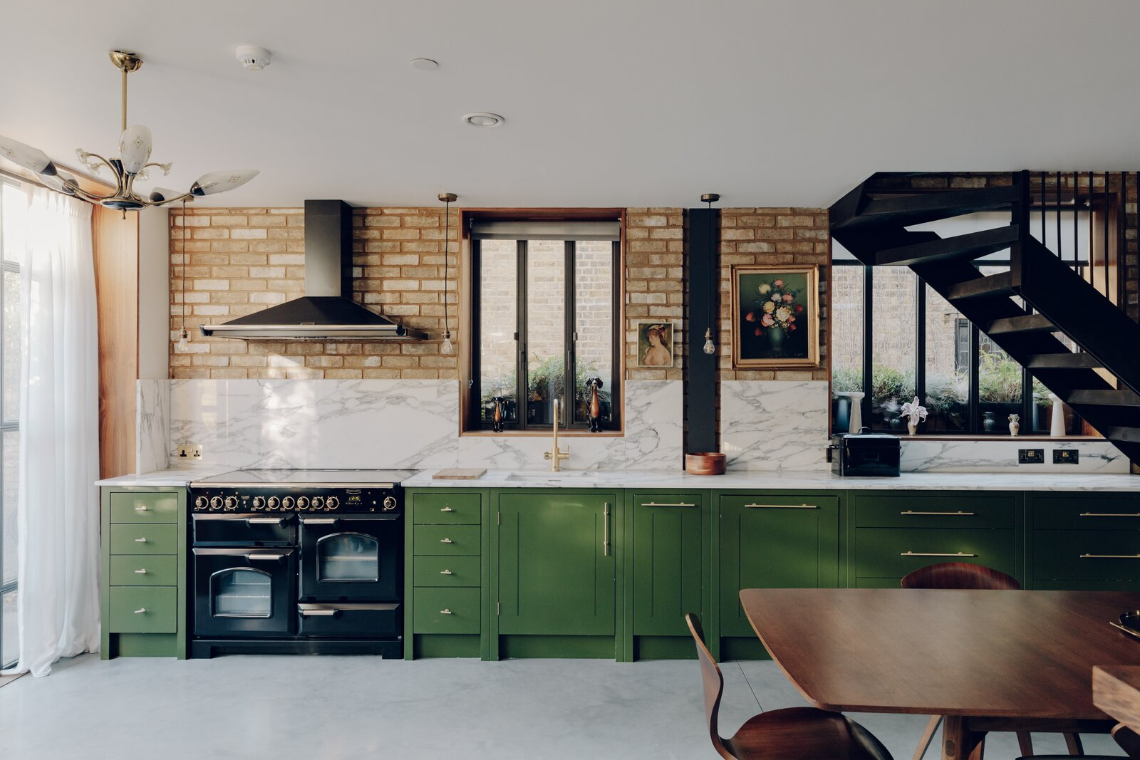 The bespoke kitchen by Plain English pairs olive green cabinetry with a marble countertop and backsplash. The exposed brick wall and concrete floor lend an edge to the material mix.  Photo 3 of 13 in An Enchanting, Reimagined Coach House in London Asks £2M
