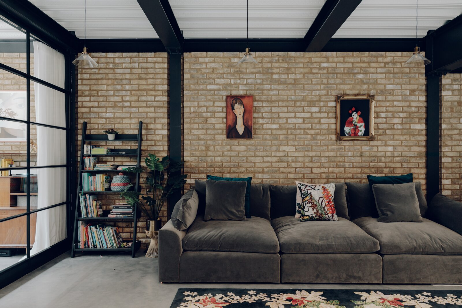 Downstairs, a separate family room is defined by exposed steel framing with inset brick walls.  Photo 6 of 13 in An Enchanting, Reimagined Coach House in London Asks £2M