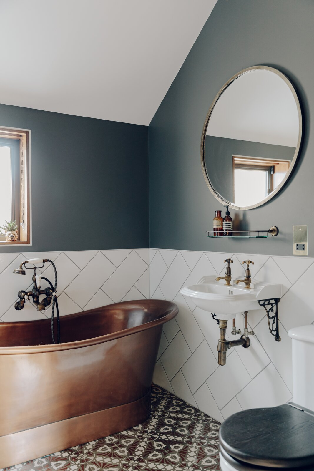The hall bathroom offers a copper tub, patterned tile floor, and traditionally styled fixtures.  Photo 12 of 13 in An Enchanting, Reimagined Coach House in London Asks £2M