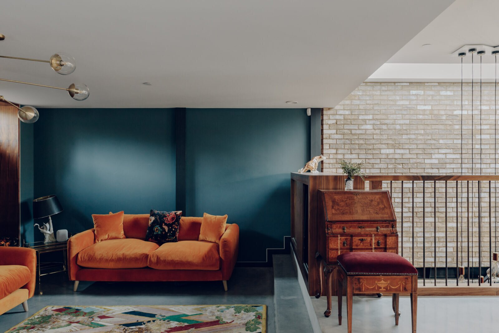 Steps down from the kitchen is the living room, delineated by a deep blue. An adjacent staircase leads to the lower-level family room, guest room, and office.  Photo 4 of 13 in An Enchanting, Reimagined Coach House in London Asks £2M