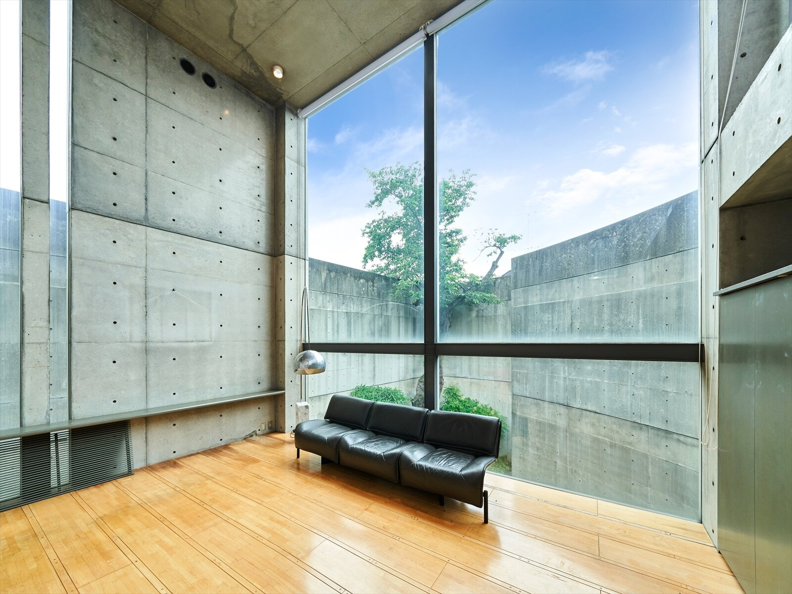 "In another unit, the living area looks out onto another courtyard featuring a large cherry tree in the corner. The room's exposed concrete walls also highlight several trademarks of Ando's work, including visible bolt holes—intentionally left over from carefully placed wall molds—as well as the varnished concrete finish described by others as ""smooth as silk.""  Photo 5 of 11 in Tadao Ando's Curved Concrete Ito House Asks $7M in Tokyo"